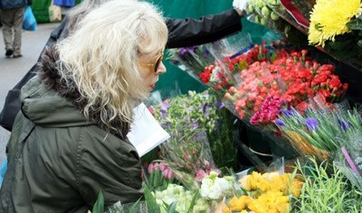 Buyer looking at flowers at Charlie's flower stall in Barnet Market