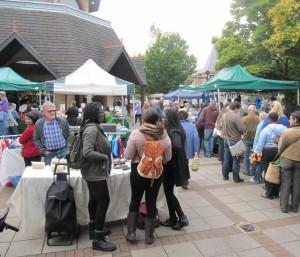 Shoppers in Barnet Market with stalls outside Waitrose