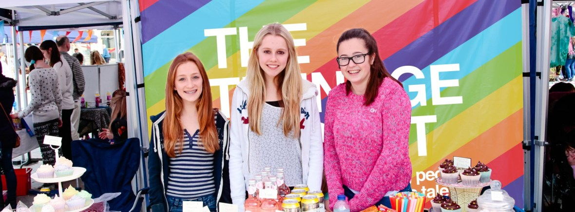 Three young stallholders standing behind their good at a Teenage Market